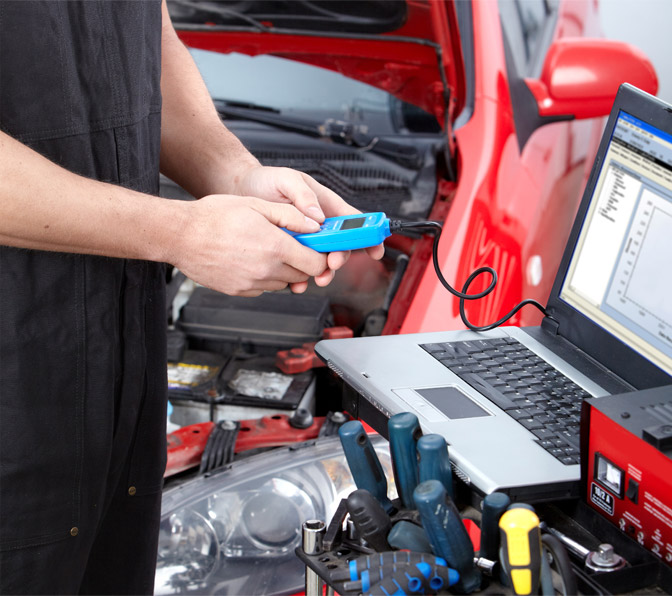 Mechanic with Laptop and Testing Equipment